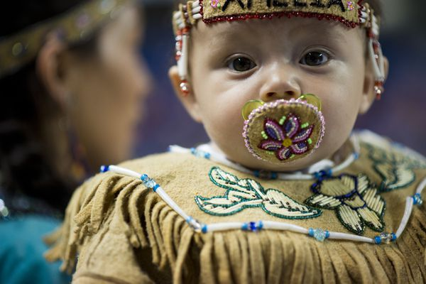 "Amelia Steele, 7 months, is carried by her mom, Chelsea Morrow. Youngsters modeled fur and skin outfits during the World Eskimo-Indian Olympics Native baby regalia competition on July 20, 2017. Mandy Sullivan, who was the event's emcee, said the designs are judged on the materials used, the craftsmanship of the garment and the crowd's reaction. Sullivan said regalia sewing is more difficult on smaller garments than larger ones, and that's one reason the event attracts interest. The tiny models, ages 6 to 36 months, are another draw. ""Everybody loves babies,"" she said. (Marc Lester / Alaska Dispatch News)"