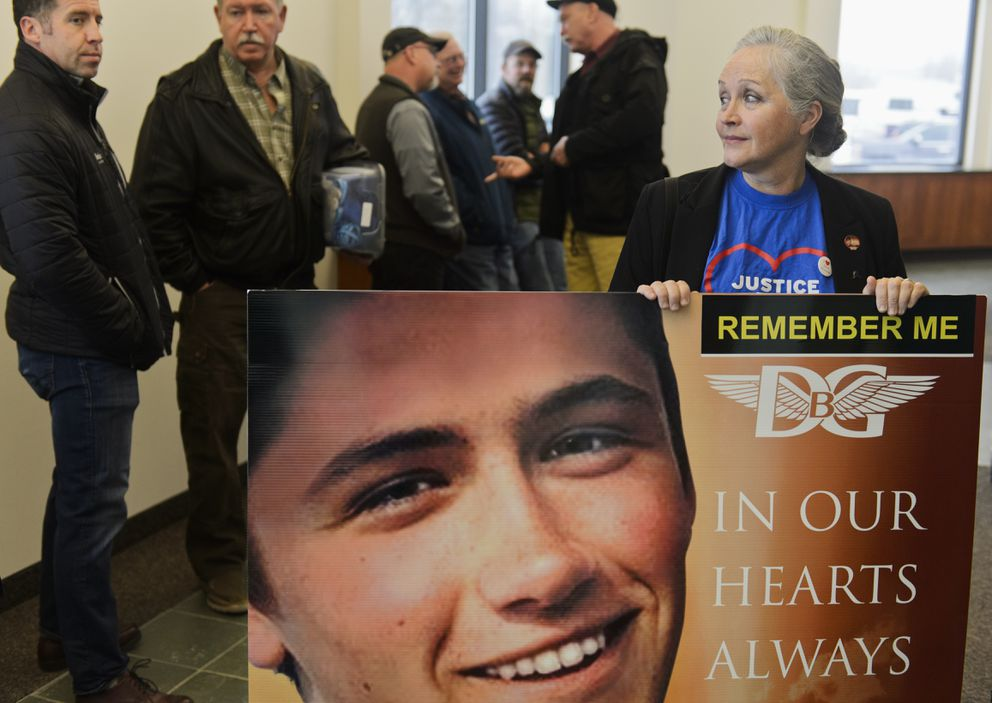 Edie Grunwald holds a board with a photo of her son David Grunwald outside a Palmer courtroom on February 5, 2020. Austin Barrett pled guilty after a plea agreement Wednesday. (Marc Lester / Anchorage Daily News)