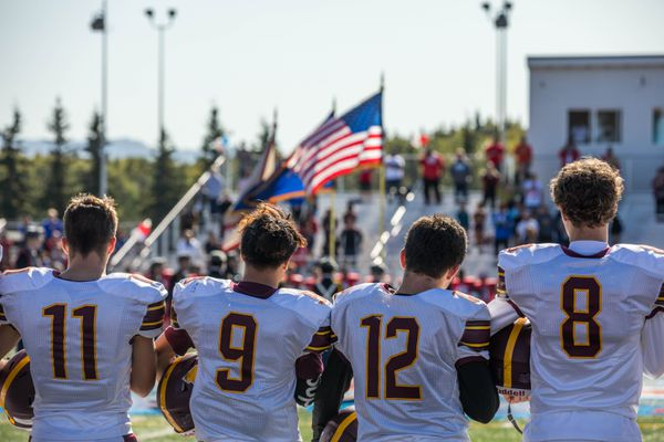Members of the Dimond high school varsity team stand for the national anthem before a game against East on Saturday at East High. East won 47-0. (Loren Holmes / ADN)