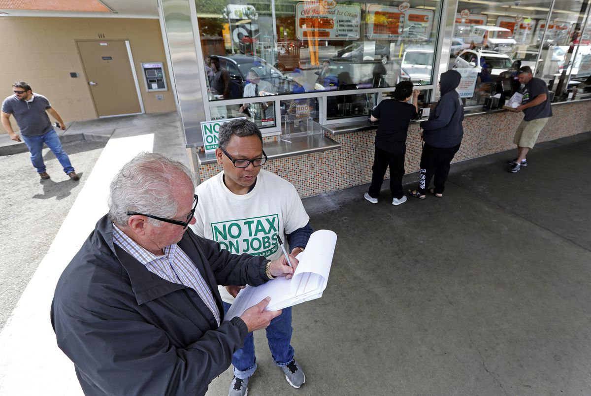 "Marvin Rosete, right, gets a signature last week to repeal the head tax from Stu Young, left, at the Wallingford Dicks Drive-In. ""How many times can I sign?"" joked Young. (Ken Lambert/The Seattle Times/TNS)"