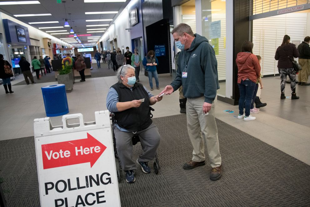 Bart Parker, a Division of Elections temporary worker, hands out a sticker Tuesday. (Marc Lester / ADN)
