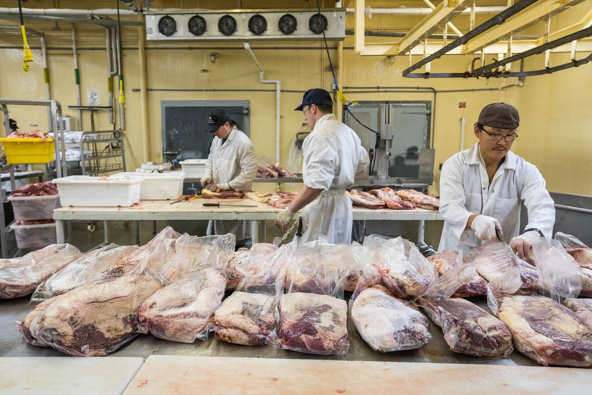 Noah Noes, right, prepares meat for processing at the Mt. McKinley Meat and Sausage Co. slaughterhouse on Nov. 18. (Loren Holmes / Alaska Dispatch News)