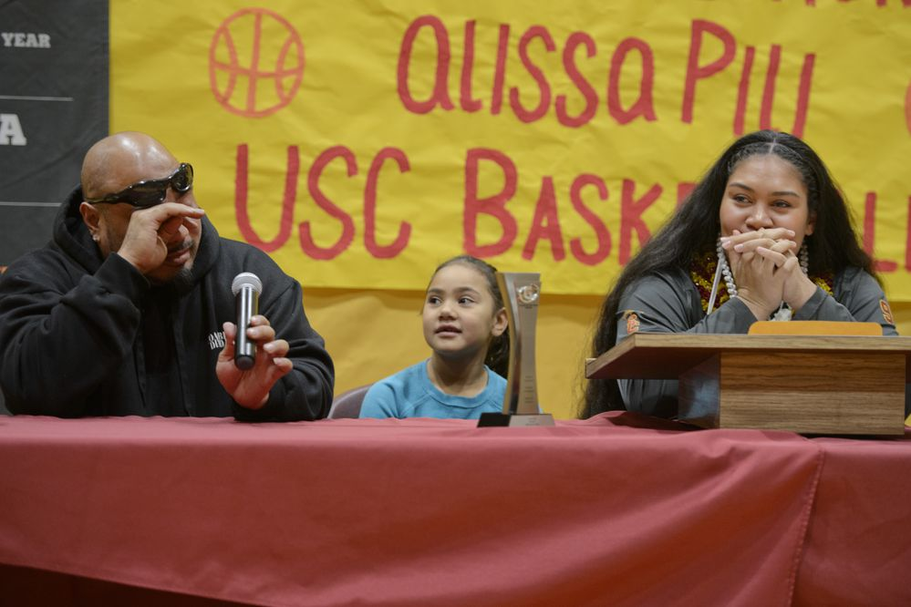 Billy Pili, left, gets choked up as he talks about his daughter Alissa Pili, right. Alissa Pili signed a National Letter of Intent to play basketball for University of Southern California during a ceremony at Dimond High School on November 14, 2018. Alissa's sister Alyna Pili is at center. (Marc Lester / ADN)