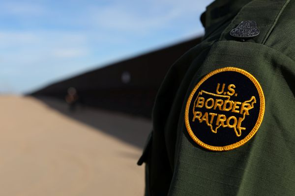 A U.S. border patrol agent walks along the border fence between Mexico and the United States near Calexico, California, U.S. February 8, 2017. Picture taken February 8, 2017. REUTERS/Mike Blake