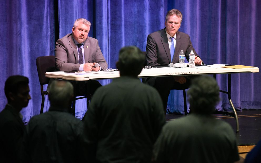 Alaska Gov. Mike Dunleavy, right, and Dunleavy community relations liasion Dave Stieren listen to a comment during a town hall meeting at the Steve Primis Auditorium at Chugiak High School on Monday, March 2, 2020 in Chugiak, Alaska. (Matt Tunseth / ADN)