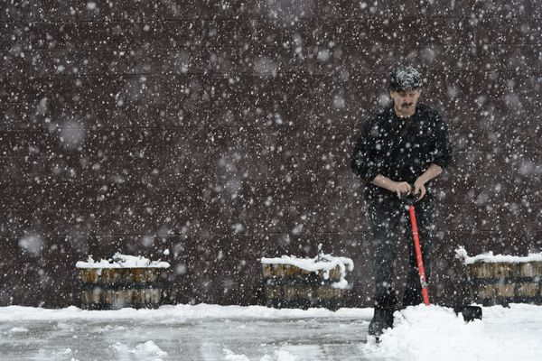 Richard Allred shovels the walkway in front of Sixth Avenue Outfitters in downtown Anchorage during a heavy snowfall on April 22, 2019. (Marc Lester / ADN)