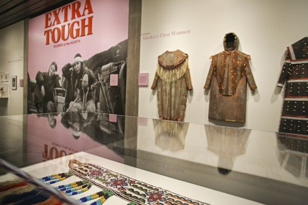 An Athabascan baby belt, bottom, and metal sculptures representing traditional dress of Alaska Native women, right, on display in 'Extra Tough: Women of the North', an exhibit at the Anchorage Museum in Downtown Anchorage. Photographed on Nov. 10, 2020. (Emily Mesner / ADN)