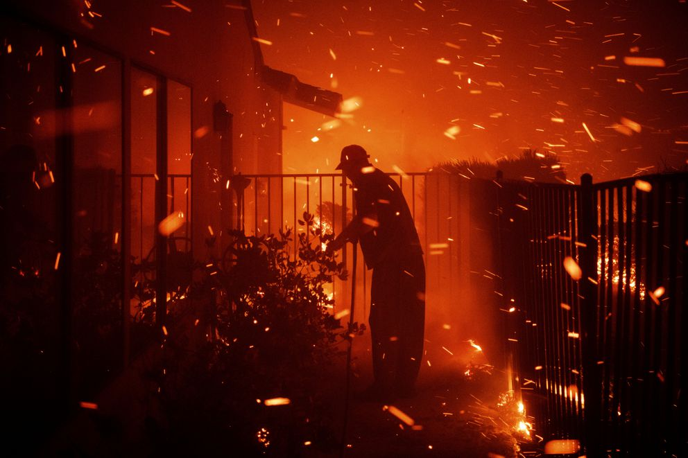 Jerry Rowe uses a garden hose to save his home on Beaufait Avenue from the Saddleridge fire in Granada Hills, Calif., Friday, Oct. 11, 2019. (AP Photo/Michael Owen Baker)