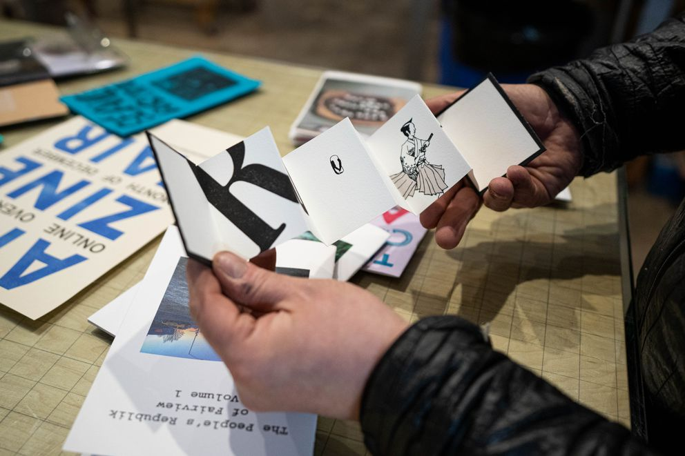 Jimmy Riordan holds 'Run ' by Shoko Takahashi at Tent City Press on Saturday, Dec. 19, 2020. Riordan is involved with the Anchorage Zine Fair, which this year has moved online due to the pandemic. Takahashi has a number of zines available through the fair. (Loren Holmes / ADN)