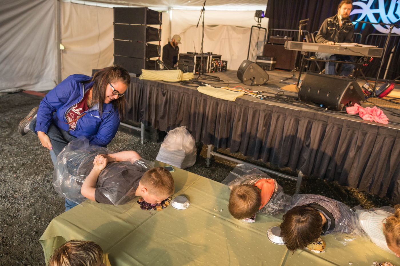 Kimberly Kennedy-Suggs holds up her son Huck Suggs's legs during a pie-eating contest Saturday, Aug. 18, 2018 at Alyeska Resort. The Blueberry Festival continues Sunday, featuring music, food, crafts and more pie-eating contests. (Loren Holmes / ADN)