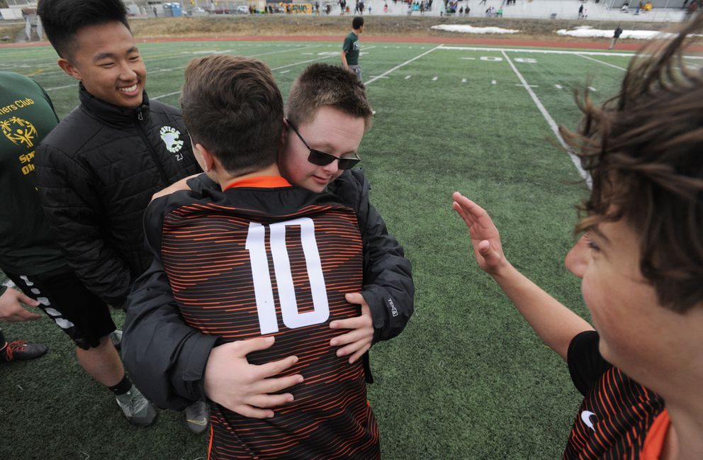 Service High athlete Chris Bagg embraces a West High varsity player after the game. (Bill Roth / ADN)