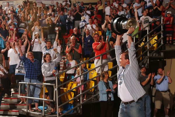 Toting the Kelly Cup, coach Davis Payne emerges from the tunnel at the conclusion of player introductions at the Alaska Aces Kelly Cup celebration Saturday evening June 3, 2006 at Sullivan Arena. (Erik Hill / Alaska Dispatch News archive 2006)
