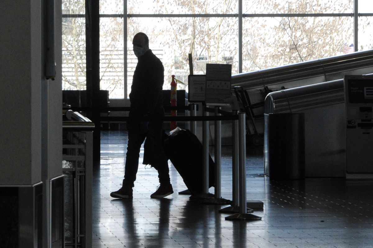 A passenger checks in at the Alaska Airlines counter at Ted Stevens Anchorage International Airport on Sunday, May 3, 2020, during the COVID-19 pandemic. (Bill Roth / ADN)