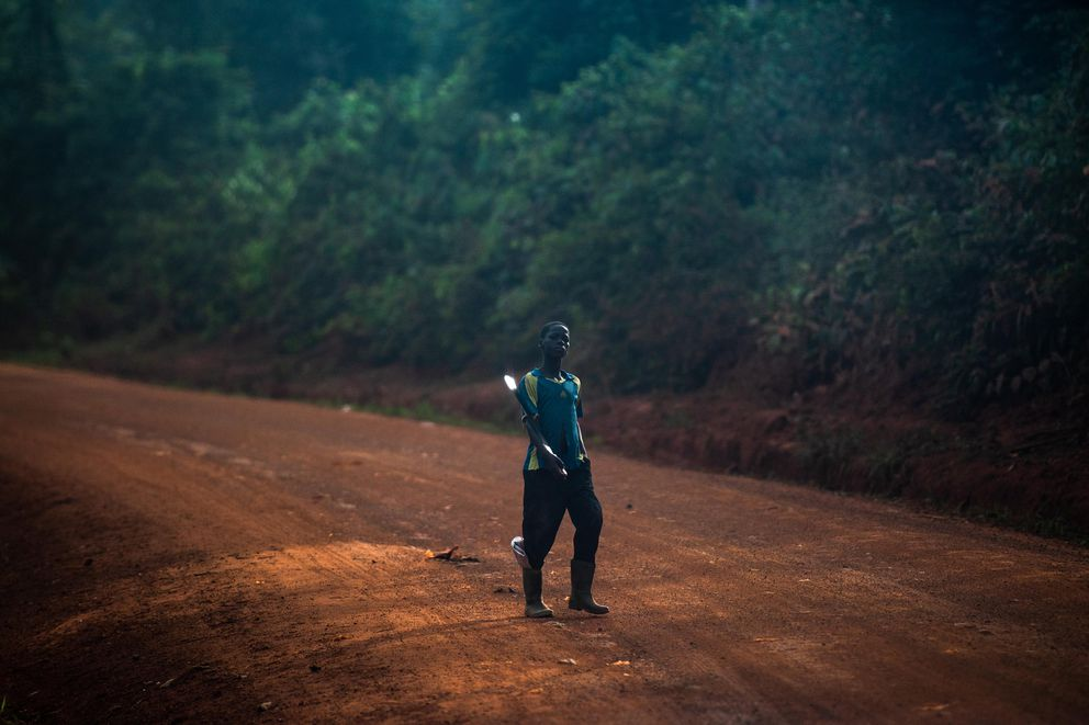A boy holds his machete as he heads along a road to a cocoa farm. (Washington Post photo by Salwan Georges)