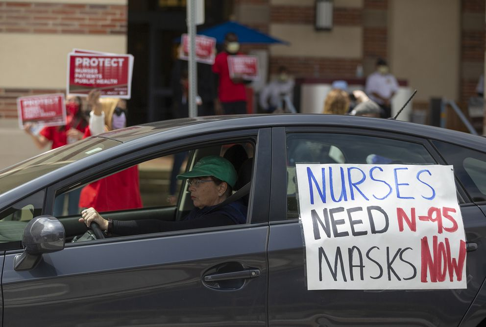 In this April 13, 2020, photo, a car passes nurses protesting the lack of N95 respirators and other Personal Protective Equipment outside the UCLA Medical Center. (AP Photo/Damian Dovarganes)