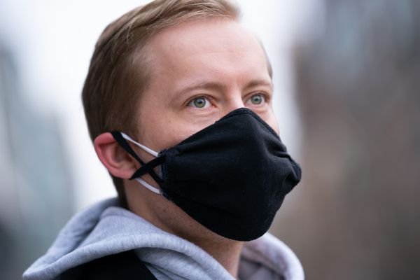 Danny Ryan, 27, is pictured wearing two masks on Wednesday near his home in Washington, D.C. Double masks are becoming a real possibility as a new virus variant makes its way from England, South Africa, and Brazil into the U.S. (Washington Post photo by Sarah L. Voisin)