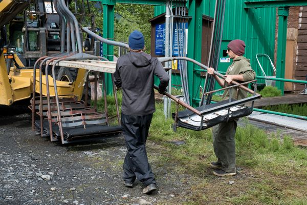 Alyeska Resort employees work together to lift one of 140 chairs onto a forklift on June 7, 2017. After removing all the chairs from the chairlift, the team will take down the supporting towers using a helicopter. (Young Kim / Alaska Dispatch News)