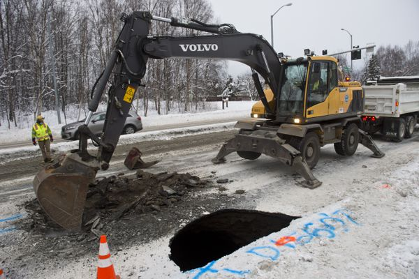 An Anchorage Water and Wastewater Utility crew respond to a sinkhole that closed westbound lanes of DeBarr Road near Hoyt Street on November 23, 2020. (Marc Lester / ADN)