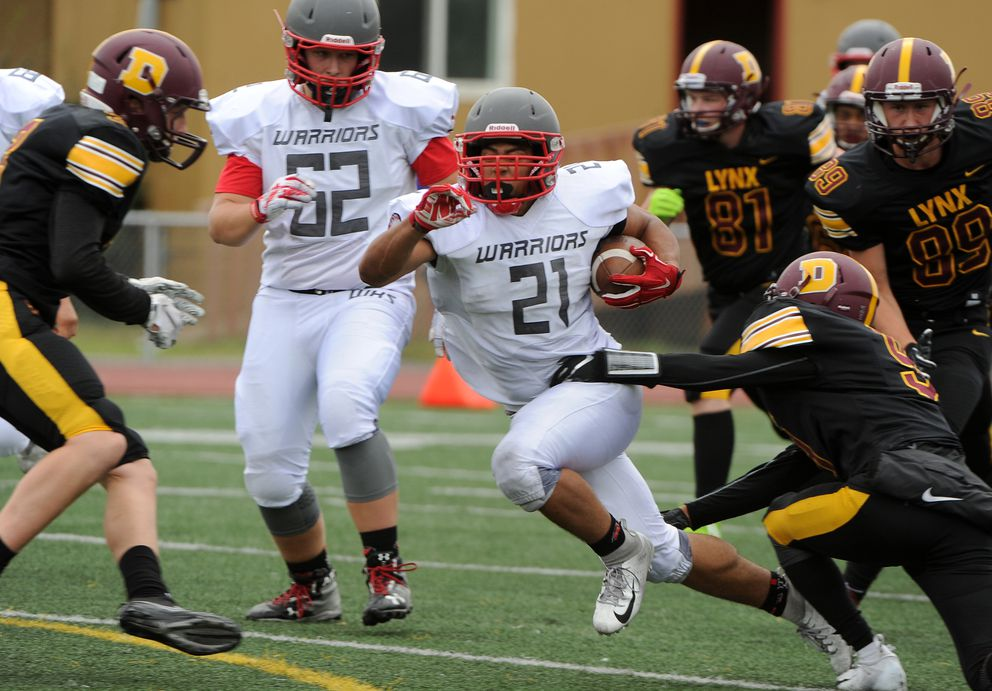 Reginald Drummond of Wasilla gains some ground as Jaili Rescober of Dimond gets a hand on him at Dimond High School in Anchorage, AK on Saturday, Aug. 11, 2018. Dimond High defeated Wasilla High 35-21 in their opening football game of the season. (Bob Hallinen / ADN)