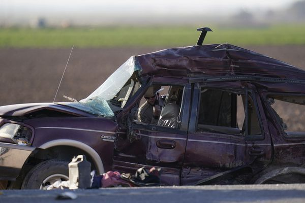 Law enforcement officers sort evidence and debris at the scene of a deadly crash in Holtville, Calif., on Tuesday, March 2, 2021. Authorities say a semi-truck crashed into an SUV carrying 25 people on a Southern California highway, killing at least 13 people. (AP Photo/Gregory Bull)
