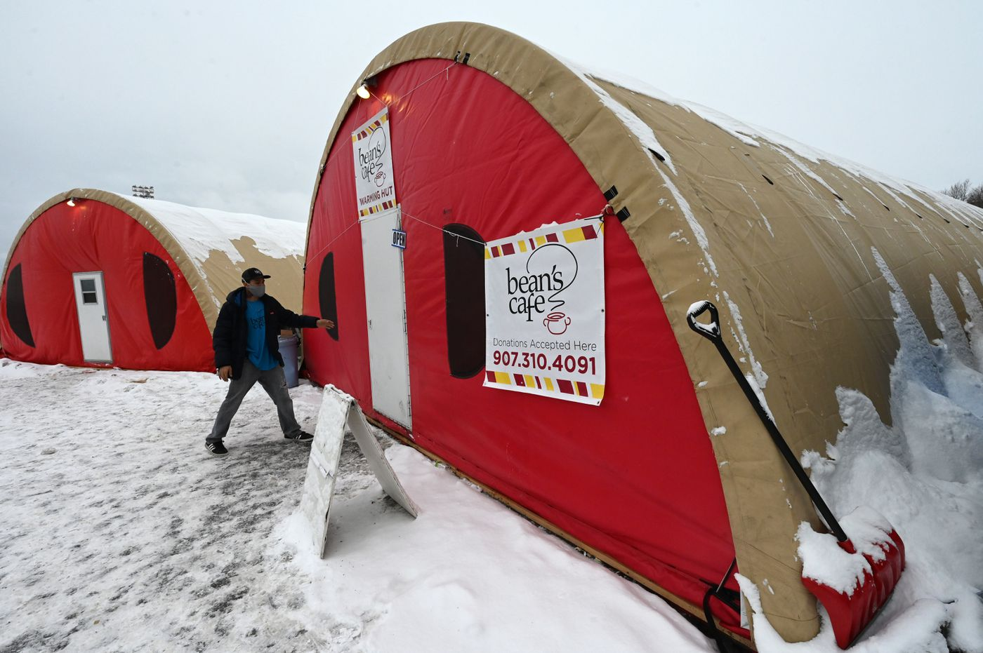 Grady Dollison, a lead monitor with Bean's Cafe, checks on one of the warming tents in Sullivan Arena parking lot on Wednesday, Feb. 24, 2021. (Bill Roth / ADN)