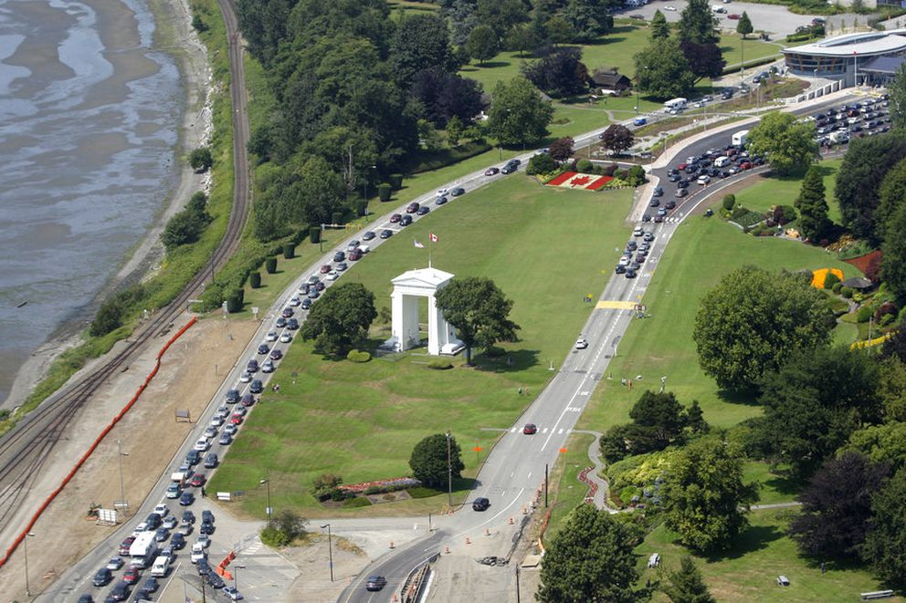 FILE - In this July 24, 2009 file photo, cars line-up heading into the United States at left and into Canada at right adjacent to Boundary Bay at a border crossing at Blaine, Wash. A 19-year-old woman who traveled from France to Canada to visit her mother in British Columbia says U.S. officials detained her for two weeks after she accidentally crossed the border while jogging. Cedella Roman tells the Canadian Broadcast Co. that two U.S. Customs and Border Protection agents apprehended her on May 21, 2018 on a beach south of White Rock, British Columbia. Roman says she didn't have identification and was transferred to the Tacoma Northwest Detention Center run by the Department of Homeland Security. (AP Photo/Elaine Thompson)