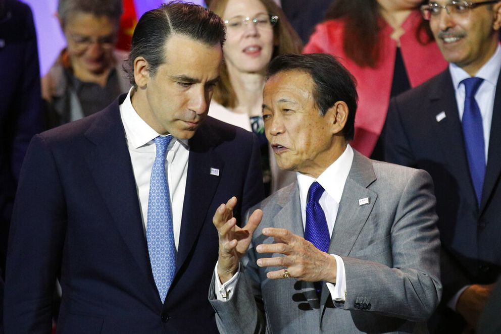 U.S. Deputy Secretary of the Treasury Justin Muzinich, left, talks with Japan's Finance Minister Taro Aso during the group photo at the Paris Forum entitled 'Sustainable Debt for Sustainable Growth ' at Bercy economy ministry in Paris, Tuesday, May 7, 2019. (AP Photo/Francois Mori)