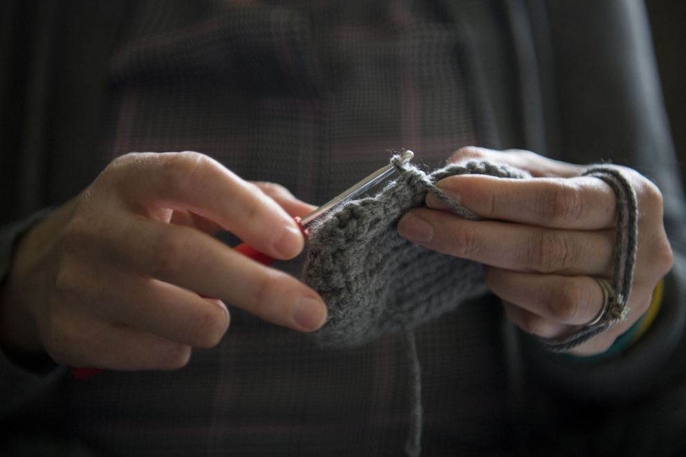 Kate Plants crochets a bootee in memory of one of the embryos she lost. Washington Post photo by Carolyn Van Houten.
