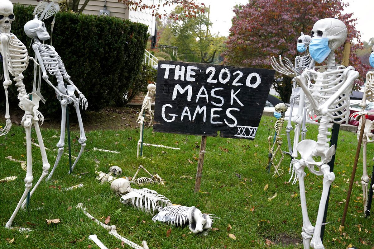 Coronavirus-themed Halloween decorations are displayed on a lawn in Tenafly, N.J. (AP Photo/Seth Wenig, File)