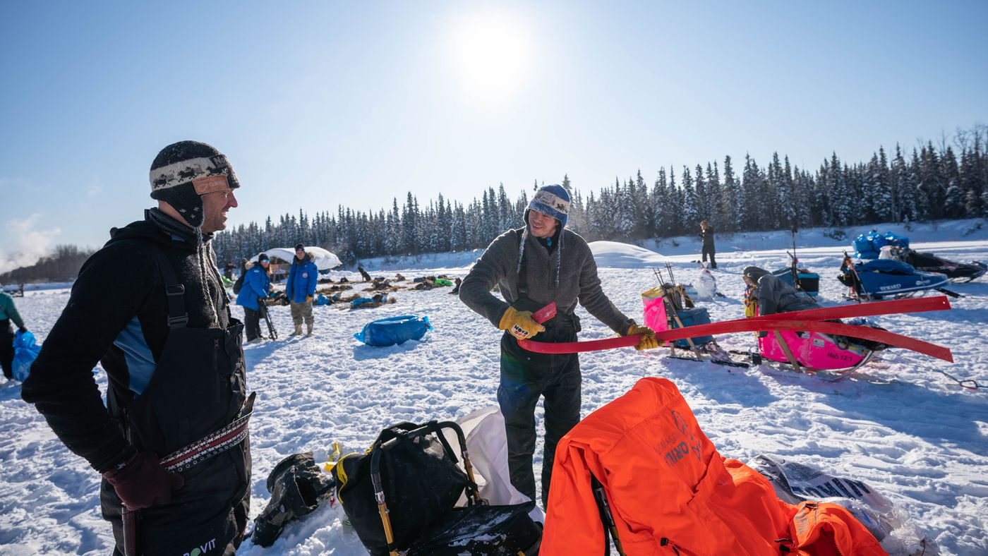 Joar Leifseth Ulsom, right, chats with fellow Norwegian musher Thomas Waerner after changing out the runners on his sled. (Loren Holmes / ADN)