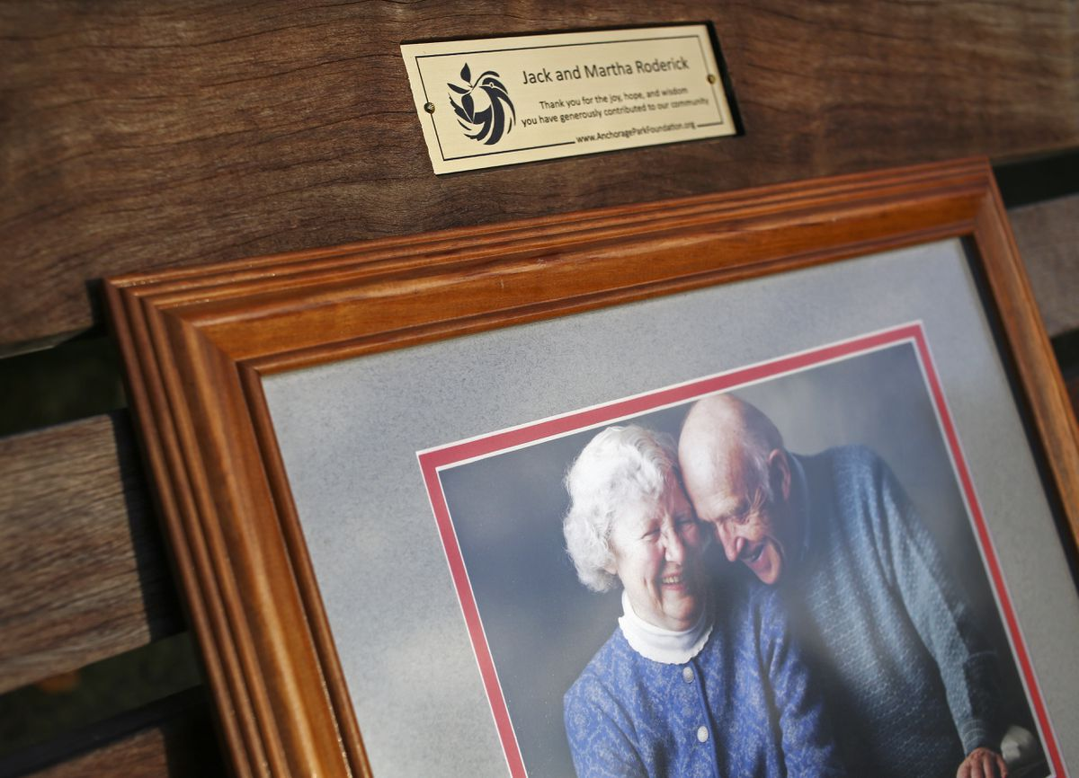A framed photograph of Jack and Martha Roderick rests on a newly installed bench along the Chester Creek Trail that honors the couple for their political and community service in Anchorage. Neighbor Alec Kay arranged for the bench with the Anchorage Park Foundation and the Municipality of Anchorage. (Emily Mesner / ADN)