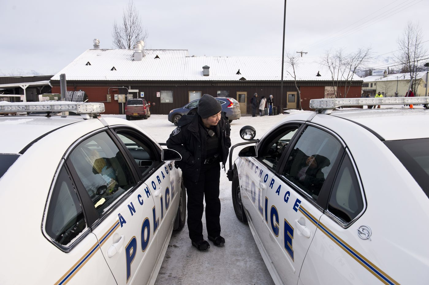 Anchorage police officer Natasha Welch talks with her colleagues outside Bean's Cafe on Jan. 10.  (Marc Lester / ADN)