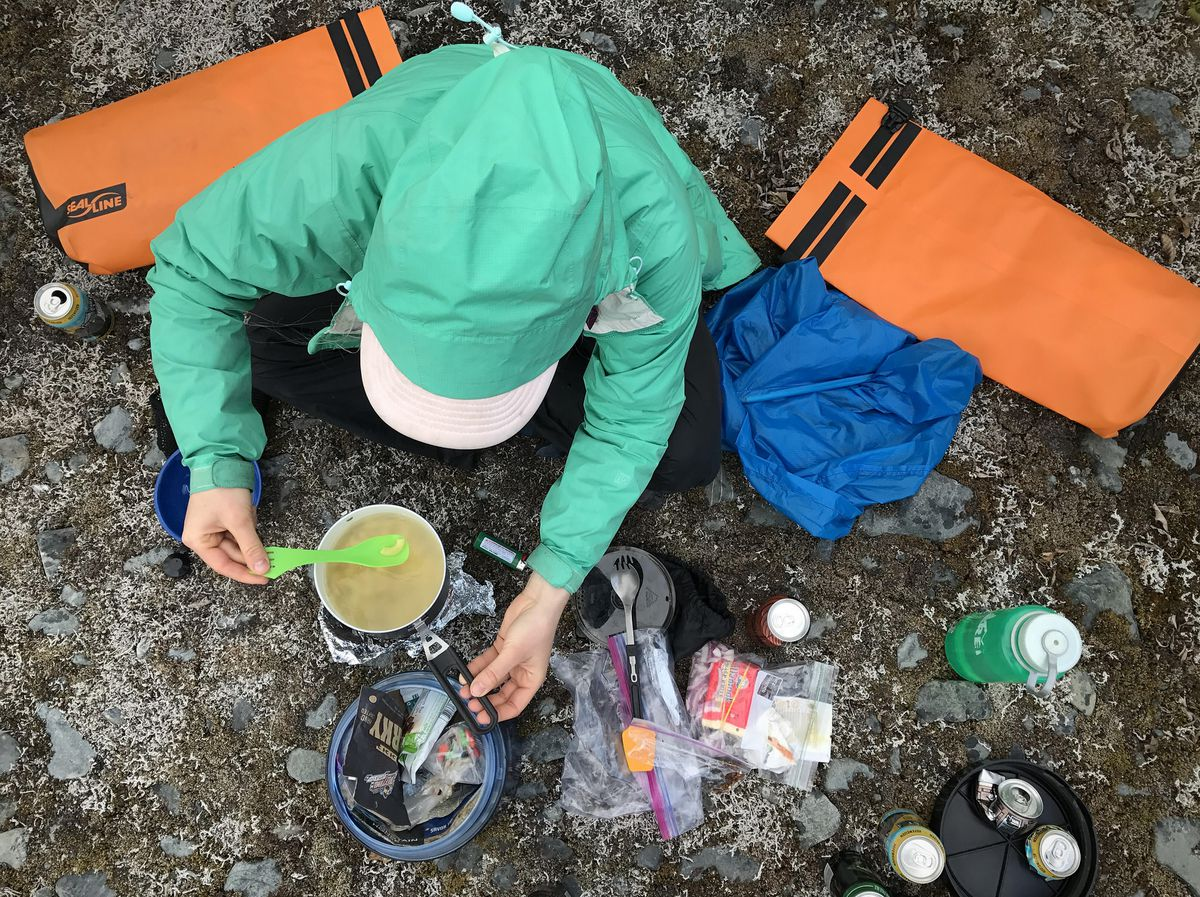 Devin Kelly prepares pasta with reindeer sausage, white cheddar and red onion near Spencer Glacier on June 11. (Vicky Ho / Alaska Dispatch News)
