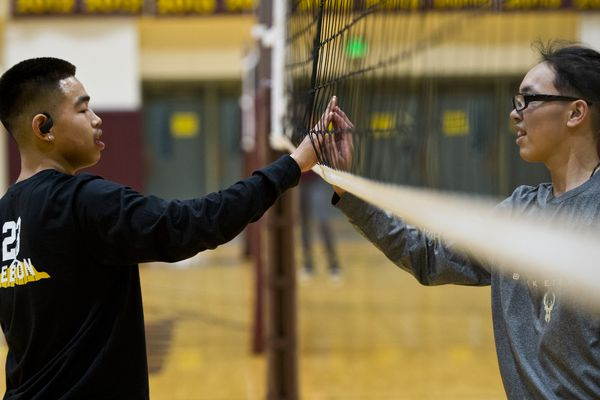 Alakanuk teammates Jeremiah Hootch, left, and Avery Ayunerak high five at the net during practice on December 4, 2019. The Mix Six Volleyball State Championships begins Thursday at Dimond High School. (Marc Lester / Anchorage Daily News)