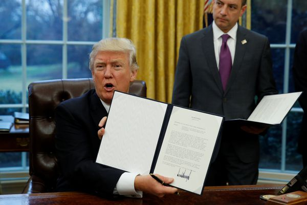 U.S. President Donald Trump holds up the executive order on withdrawal from the Trans Pacific Partnership after signing it as White House Chief of Staff Reince Priebus stands at his side in the Oval Office of the White House in Washington January 23, 2017. REUTERS/Kevin Lamarque