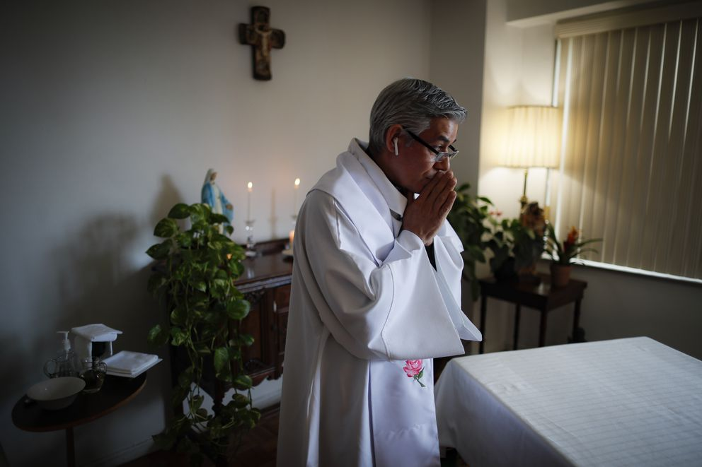 Fabian Arias, a Lutheran pastor with Saint Peter's Church in Manhattan, prepares to give Sunday services at his home via an internet livestream broadcast, Sunday, May 10, 2020, in the Bronx borough of New York. (AP Photo/John Minchillo)