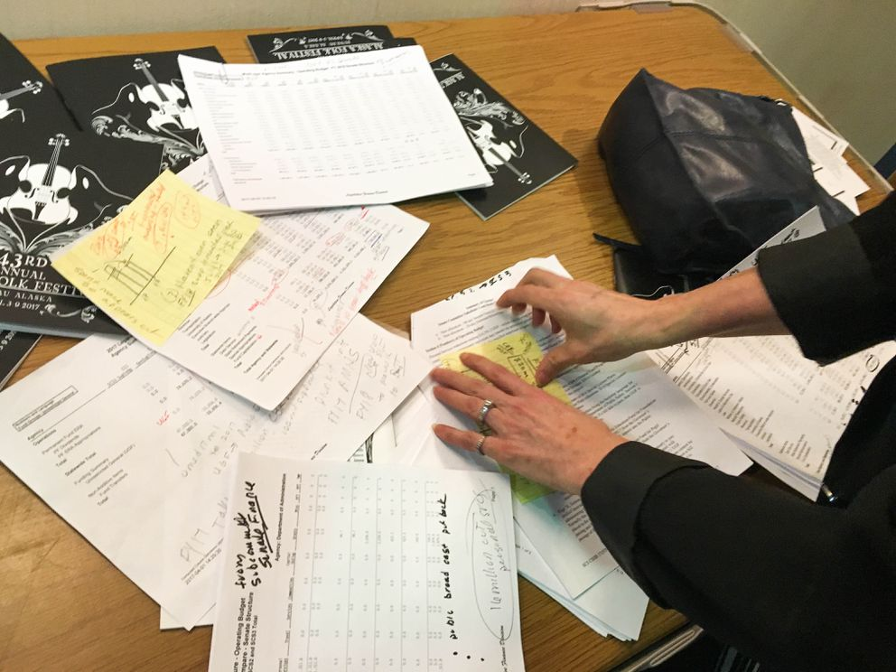 Eagle River Republican Rep. Lora Reinbold, during a break from the Juneau folk festival this week, shows a reporter the tables she's using to analyze the Alaska Senate's new budget proposal. (Nathaniel Herz / Alaska Dispatch News)