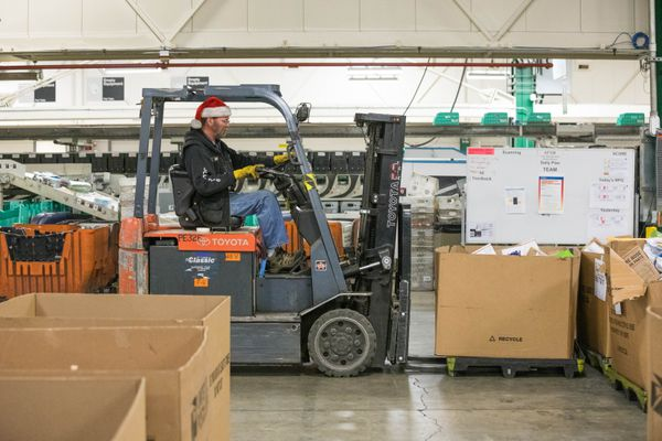United States Postal Service employee Roger King, wearing a Santa hat, moves packages in the Anchorage main office on Friday, Dec. 14, 2018. The office, Alaska's largest, is expecting to handle 5 million packages this holiday season. (Loren Holmes / ADN)