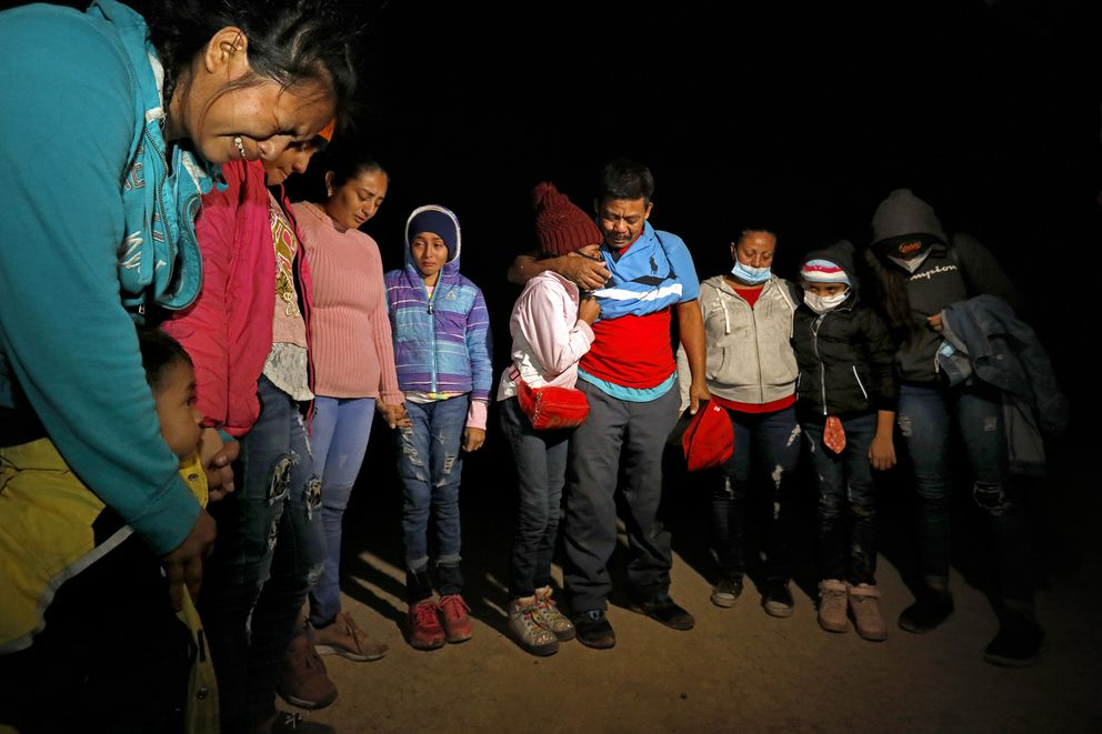 Migrants who have just been smuggled across the Rio Grande River stop to pray before continuing on their way to seek asylum in the United States on Friday, March 26, 2021 in Roma, Texas. (Carolyn Cole/Los Angeles Times/TNS)
