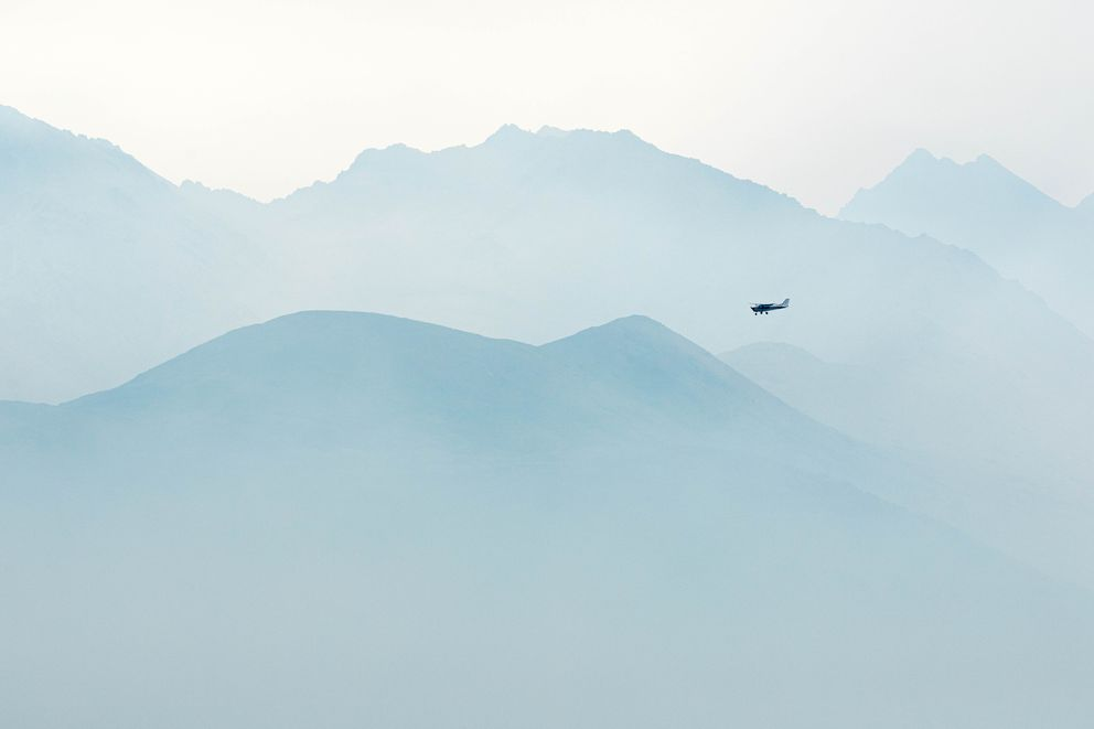 A small airplane approaches Merrill Field in front of smoke-obscured mountains Tuesday, Aug. 20, 2019. Smoke from Southcentral Alaska wildfires has recently led to poor air quality in Anchorage. (Loren Holmes / ADN)