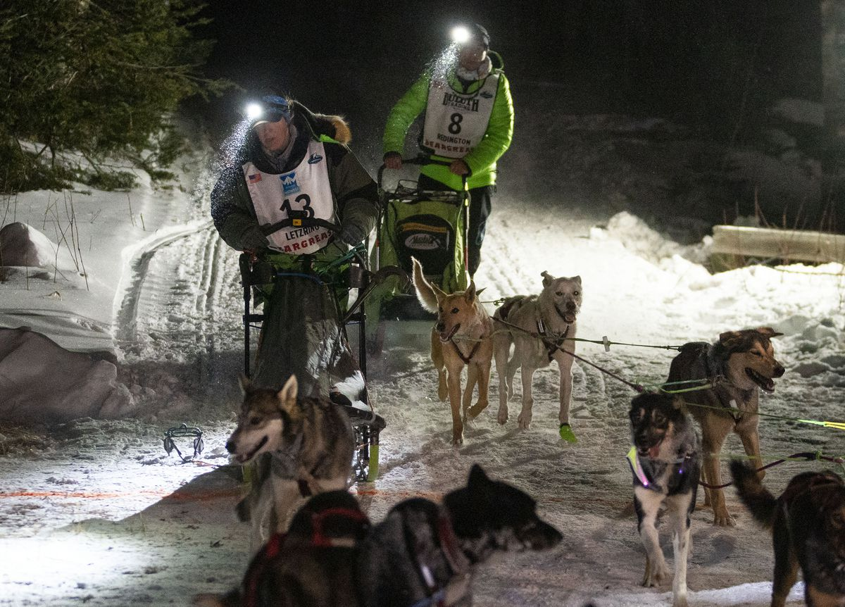 Erin Letzring crosses the finish line with defending champion Ryan Redington right behind her to take a seven-second victory Tuesday in the 330-mile Beargrease Sled Dog Marathon in Minnesota. (Alex Kormann/Star Tribune via AP)