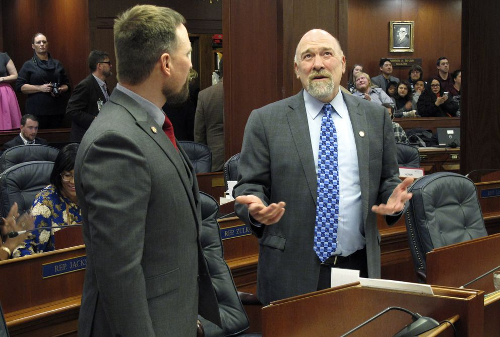 Alaska state Rep. Ben Carpenter, R-Nikiski, left, and Rep. Adam Wool, right, D-Fairbanks, chat on the House floor before the start of the 2020 legislative session, Tuesday, Jan. 21, 2020, in Juneau, Alaska. (AP Photo/Becky Bohrer)