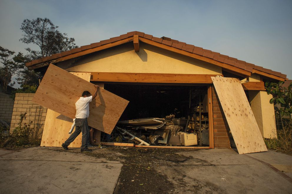 Judy Webber has her Beaufait Avenue fire damaged home in the Porter Ranch area of Los Angeles boarded up after the Saddleridge Fire burned thousands of acres during Santa Ana wind conditions, Friday, Oct. 11, 2019. (Sarah Reingewirtz/The Orange County Register/SCNG via AP)