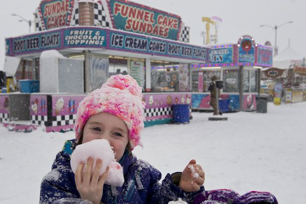 Charlotte Dodson, 5, enjoys some cotton candy while visiting the carnival with her father, Jay Dodson. A heavy snowfall kept the crowds light at the Fur Rondy Carnival in downtown Anchorage on Feb. 26, 2018, but Golden Wheel Amusements employees worked to keep the rides ready to go. The Fur Rondy Carnival continues through March 4 at 3rd Avenue and E Streets. (Marc Lester / ADN)