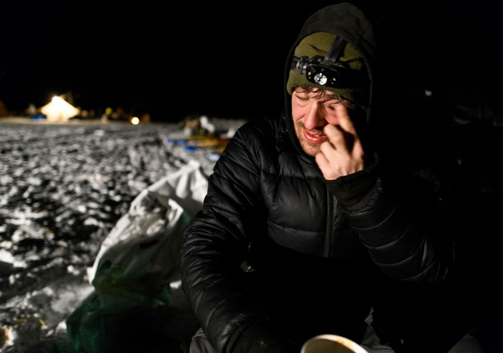 Richie Beattie sips coffee while preparing to leave Nikolai during the Iditarod Trail Sled Dog Race on March 5, 2019. (Marc Lester / ADN)