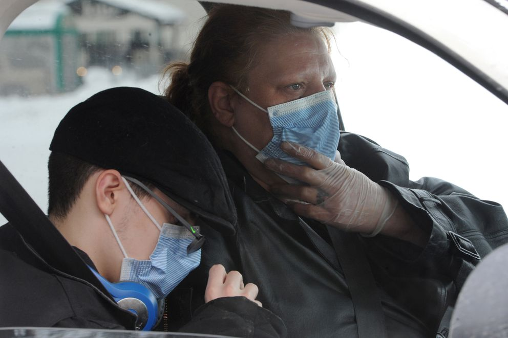 Suezanne Keller and her son Kaleb wait in their car to receive a family meal kit during the Children's Lunchbox pantry box distribution by Bean's Cafe at the Fairview Recreation Center on Wednesday, March 18, 2020. (Bill Roth / ADN)