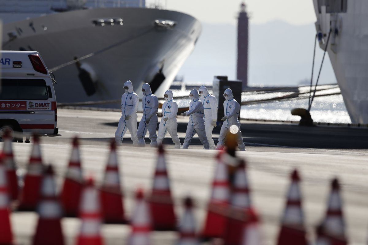 In this Feb. 11, 2020, file photo, medical workers with protective suites walk away from the quarantined Diamond Princess cruise ship in Yokohama, near Tokyo. (AP Photo/Jae C. Hong, File)