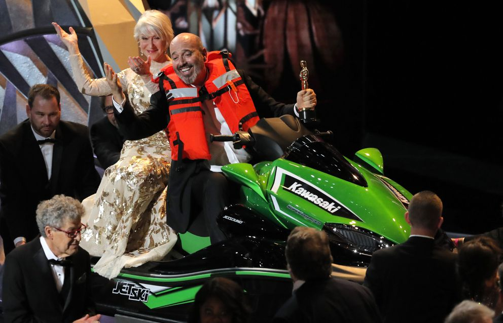 Best Costume Design winner Mark Bridges rides a jet ski with actress Helen Mirren on the back after he won it for the shortest Oscar acceptance speech of 2018. REUTERS/Lucas Jackson