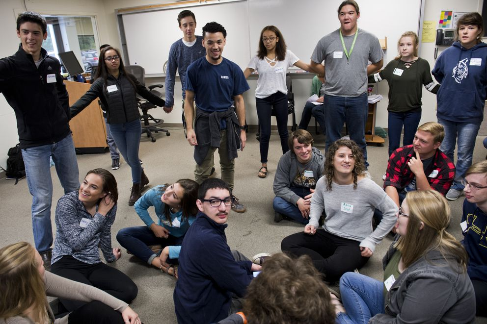 Zavier Alers, standing near center in blue t-shirt, leads an icebreaking exercise for students of Alaska Middle College School on August 21, 2017. The first day of the school year in the Anchorage School District was also the first day for its new program, Alaska Middle College School. About 150 students meet at UAA's Chugiak-Eagle River campus to earn high school and college credit simultaneously. (Marc Lester / Alaska Dispatch News)