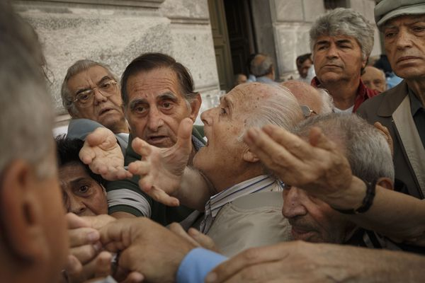 Pensioners try to get a number to enter inside a bank in Athens, Wednesday, July 1, 2015. About 1,000 bank branches around the country were ordered by the government to reopen Wednesday to help desperate pensioners without ATM cards cash up to 120 euros ($134) from their retirement checks. Eurozone finance ministers were set to weigh Greece's latest proposal for aid Wednesday.